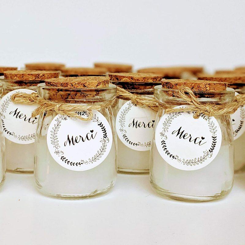 Velitas en tarro de cristal con etiqueta que pone Merci cordel y tapa de corcho